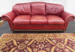 Very Plush Cordovan Leather Sofa And Oriental Style Rug. Leather Camel Back  Sofa Has Large Nail Head Trim And Carved Wooden Feet And Baseboard.